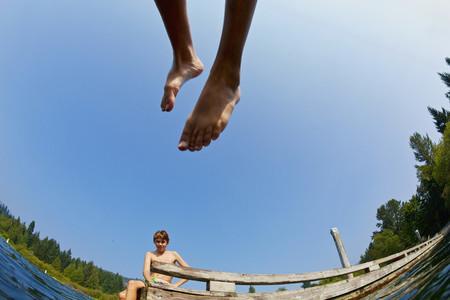 Boys jumping of dock into sunny summer lake 02