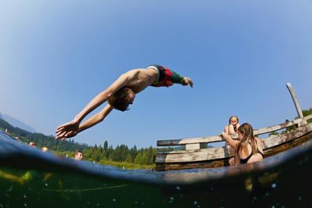Boy diving into sunny lake 01