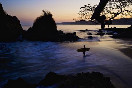 Silhouette boy with surfboard on ocean beach 01