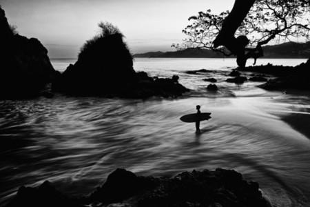 Silhouette boy with surfboard on ocean beach 02