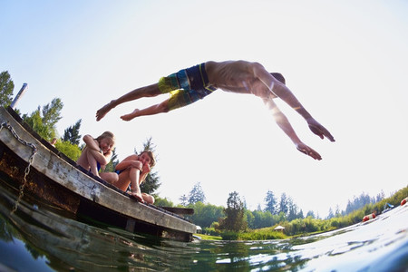 Boy jumping off dock into sunny summer lake 01