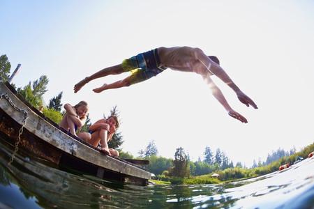 Boy jumping off dock into sunny summer lake 01