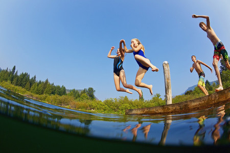 Kids jumping into sunny summer lake 01