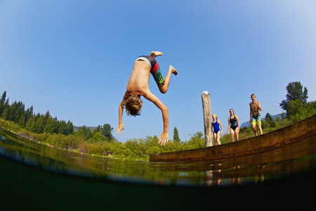 Boy somersaulting off dock into sunny summer lake 01