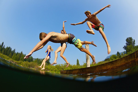 Playful kids jumping off dock into sunny summer lake 01