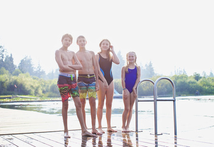 Portrait tween friends in bathing suits standing on sunny lake dock 01