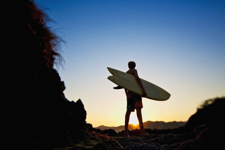 Silhouette boy with surfboard on idyllic beach at sunset 01