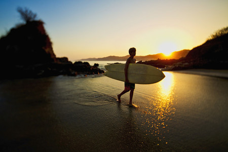 Silhouette boy with surfboard walking on idyllic ocean beach 01
