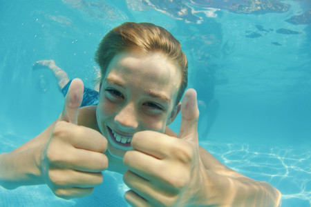Portrait happy carefree boy swimming underwater in swimming pool 01