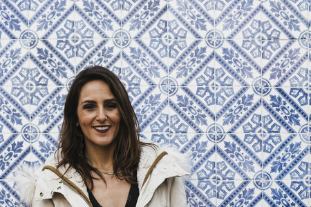 Portrait happy woman standing against blue and white mosaic wall 01