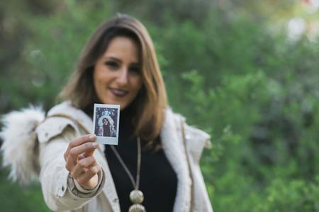 Portrait woman showing instant photograph 01