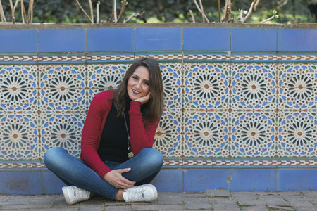 Portrait smiling woman sitting along mosaic wall 01