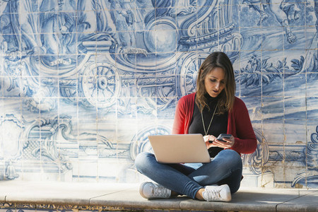 Woman using laptop and smart phone against mosaic wall 01