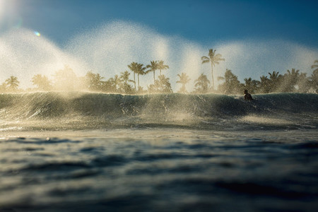 Male surfer paddling out over breaking wave on ocean at sunrise 01