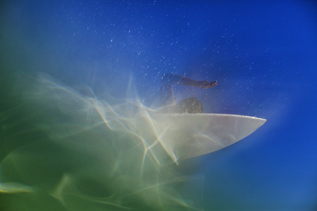 Underwater view of female surfer paddling out on surfboard 01