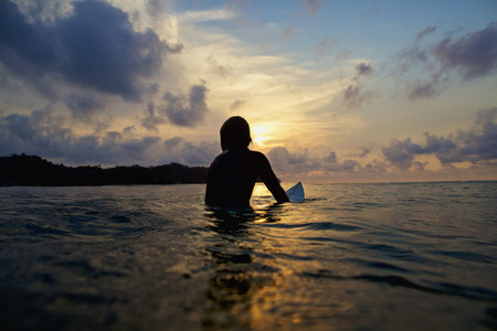 Silhouette surfer sitting on surfboard in tranquil ocean at sunset 01