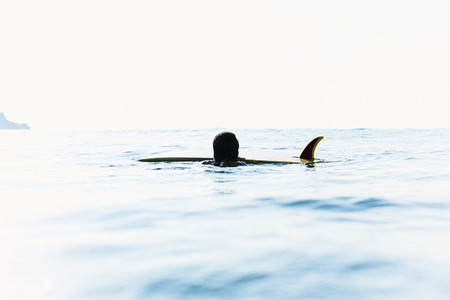 Surfer and surfboard with fin in sunny ocean 01