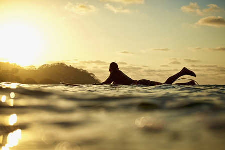 Male surfer laying on surfboard on sunny ocean at sunset 01
