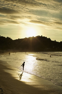 Silhouette boy wading in ocean surf on tranquil beach at sunset 01