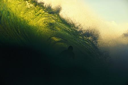 Male surfer getting barreled by ocean wave 01