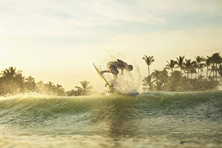 Male surfer catching air behind ocean wave at sunrise 01