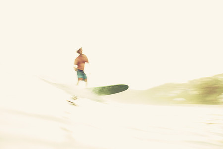 Male surfer riding wave on sunny ocean 01