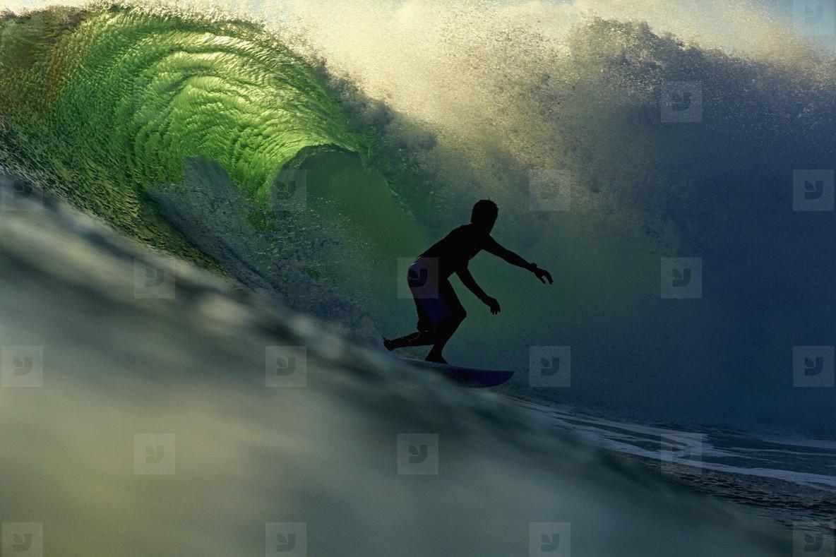 Silhouette male surfer riding backlit ocean wave  01