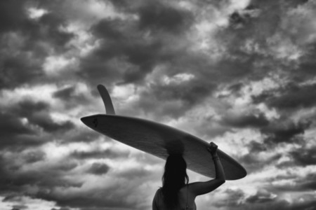 Female surfer carrying long board overhead under cloudy sky 01