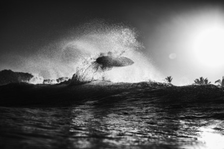 Surfer catching air behind ocean wave at sunrise 01