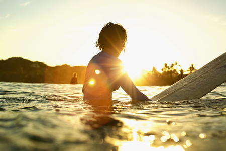 Female surfer on surfboard on sunny ocean at sunrise 01
