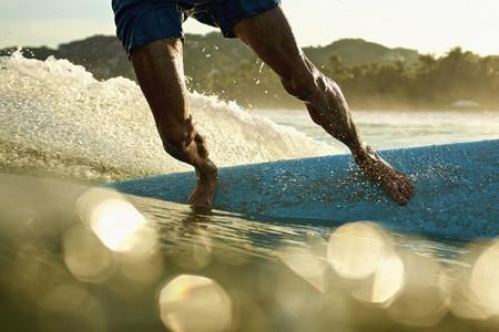Male surfer on surfboard on sunny sunrise ocean 01