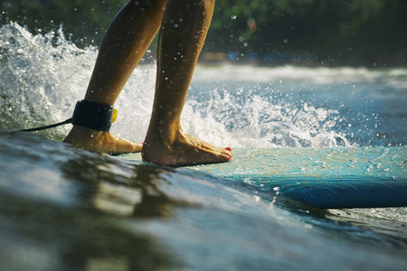 Female surfer riding surfboard on sunny ocean 01