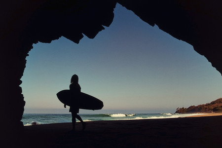 Silhouette female surfer in cave on sunny ocean beach 01