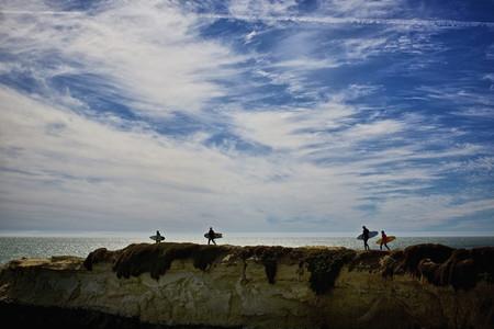 Surfers carrying surfboards on ocean rocks 01