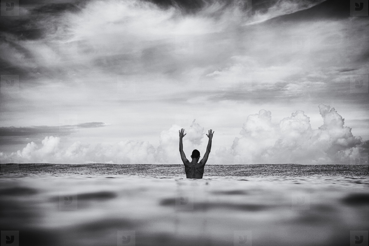 Surfer stretching arms overhead in ocean  01