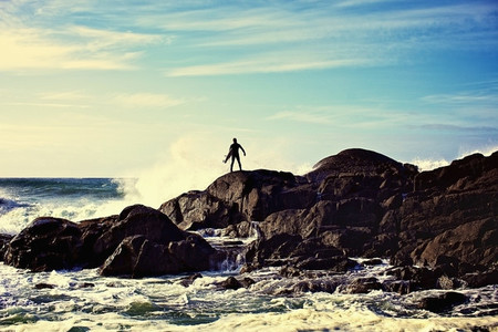 Silhouette male surfer watching ocean waves crash against rocks on sunny beach 01