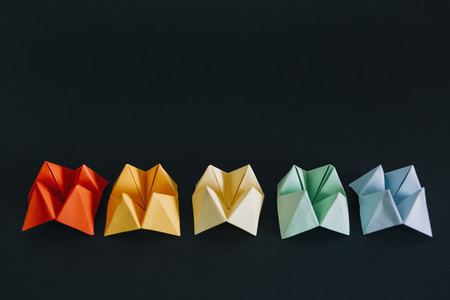 Rainbow multicolored origami fortune tellers on black background 01