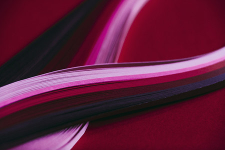 Abstract rainbow paper wave pattern on red background 01
