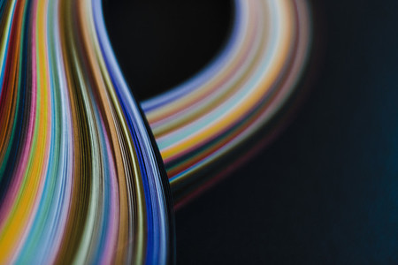 Abstract rainbow paper wave pattern on black background 01