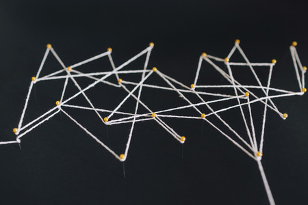 Straight pins and thread forming geometric pattern on black background 01