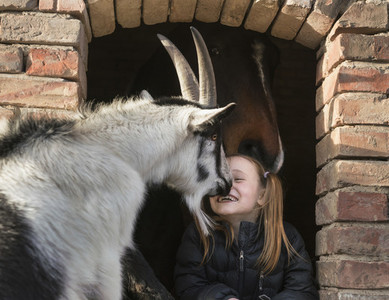 Happy girl with goat and horse in barn window 01