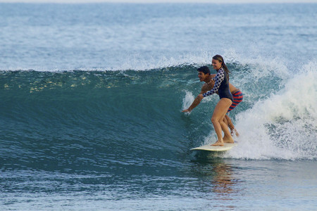 Young couple sharing surfboard 01