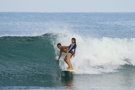 Young couple sharing surfboard 02