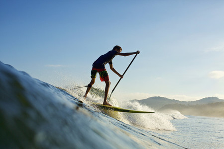 Boy paddleboarding over ocean wave 01