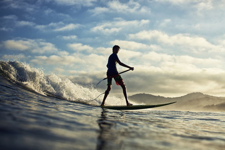Silhouette boy paddleboarding over ocean wave 01