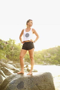 Portrait confident fit young woman standing on ocean rock 01