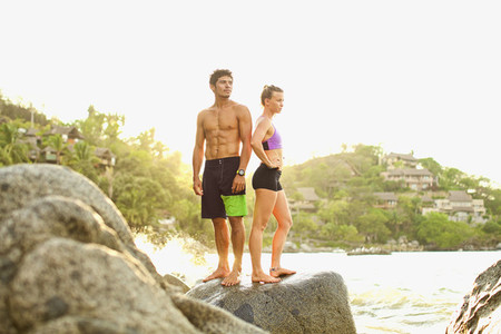 Young fit couple standing on ocean rocks 01