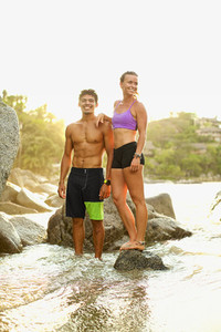Young fit couple standing on ocean rocks 02