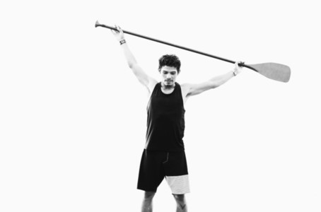 Young fit man holding oar overhead 01