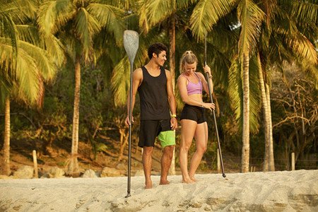 Young couple with oars on sunny tropical beach 01